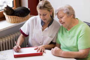 caregiver helping her patient making a letter
